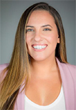 Giselle Gutierrez headshot, Latina Woman in a pink blazer with a white blouse, long brown hair, brown eyes, big smile
