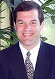 Photo of a smiling Caucasian male in front of a group of plants, wearing a dark colored suit, white button down, and patterned neck tie.