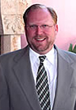 Photo of a smiling Caucasian male standing outdoors, wearing a gray suit, white button down, and striped neck tie.
