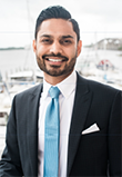 Jay R. Thakkar headshot of a young smiling Asian man in a black suit with a white shirt and light blue tie, there is a marina with boats and water in the background