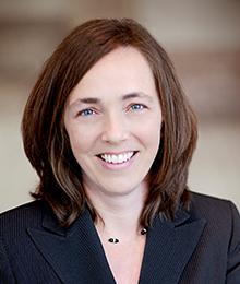 Kristin Norse headshot, Caucasian businesswoman with brown hair wearing a dark navy suit
