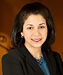 Michelle Bedoya Barnett headshot, business woman with brown hair wearing a black suit with a blue shirt and necklace, pictured in front of a brown backdrop
