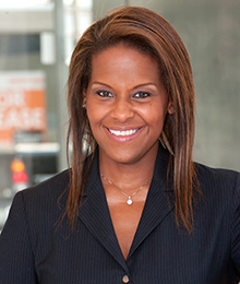 Michelle Delancy headshot, a smiling African American woman wearing a black suit, pictured in front of a window