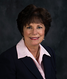 Michelle Jernigan headshot, Caucasian woman with short brown hair, wearing a black suit and pink button down shirt, pictured in front of a dark gray backdrop