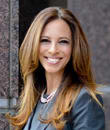 Michelle Suskauer headshot, young businesswoman smiling, she is photographed outdoors in front of a building, wearing a professional gray outfit and pearls