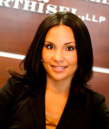 Niva Hiller-Harney is a young professional businesswoman wearing a black suit pictured in front of a brown wall