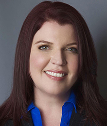 Renee Thompson headshot, Caucasian woman wearing business attire with a bright blue button down shirt, she has brown hair and is pictured in front of a solid gray backdrop