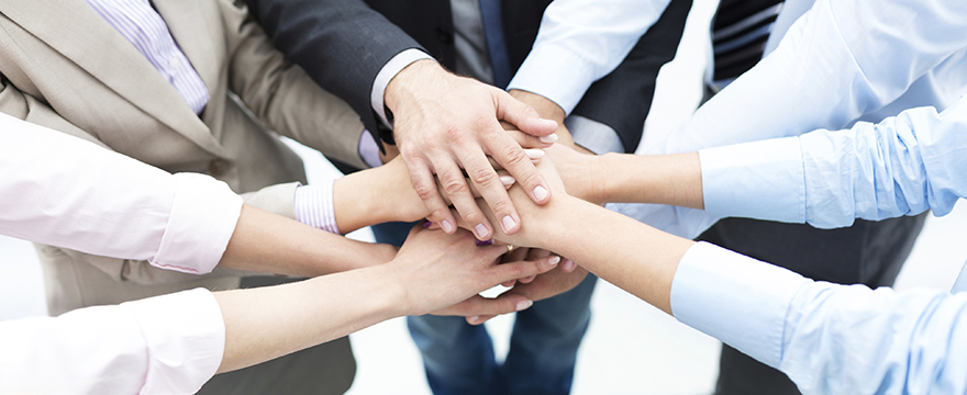 A group of people wearing business attire all holds their hands on top of one another to signify a unified team