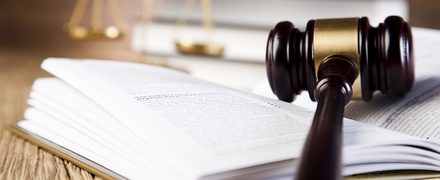 Close up of a wood and gold gavel resting on an open page of a hardcover book, scales and another book are blurred in the background
