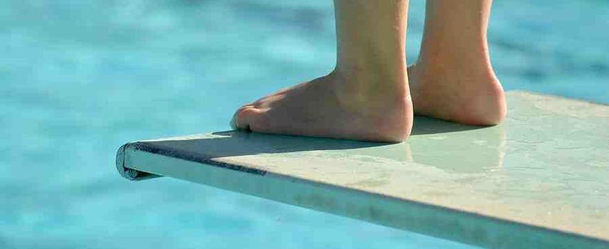 Close up image of feel standing on a diving board, over a swimming pool
