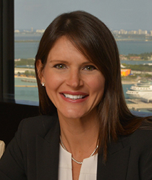 Deborah Baker Egozi headshot, Caucasian female with brown hair, wearing a white shirt under a black blazer, pictured in front of a window that overlooks a lake