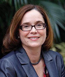 Debra Henley headshot, Caucasian woman photographed outdoors in front of a plant, she's wearing glasses and a navy suit