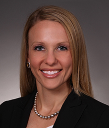 Elisa D'Amico headshot, Caucasian female with blonde hair wearing a black blazer and pearls, pictured in front of a beige backdrop