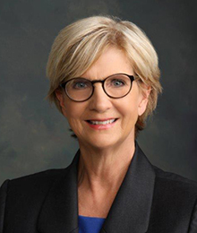 Elizabeth King headshot, Caucasian middle aged woman wearing glasses and a black suit, pictured in front of a solid gray background