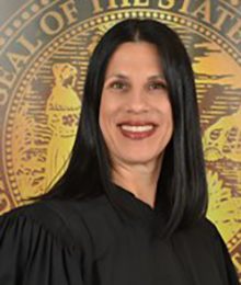 Honorable Laura Anne Stuzin, pictured in front of a large gold seal wearing a standard black academic judge gown