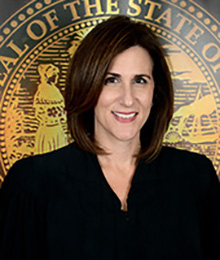 Honorable Lisa Walsh headshot, Caucasian female with short dark brown hair is pictured in front of a government seal