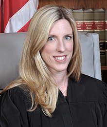 Honorable Stacy Ross headshot, middle aged Caucasian female with blonde hair is seated on a large office chair with law books and an American flag in the background