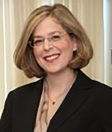 Julie Braman Kane headshot, Caucasian businesswoman is smiling, wearing a black suit and glasses