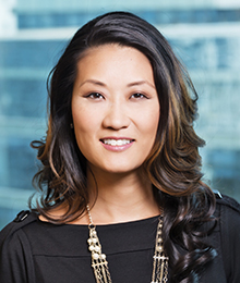 Katie Phang headshot, Asian businesswoman with long dark hair is wearing a black top with a statement necklace, pictured in front of a blue background