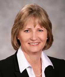 Kelly Sullivan headshot, Caucasian business woman with sandy blonde hair is wearing an black suit with a white button down shirt