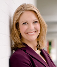 Melanie Griffin headshot, professional looking Caucasian woman leaning against a wall, smiling, she has blonde hair and is wearing a plum colored suit