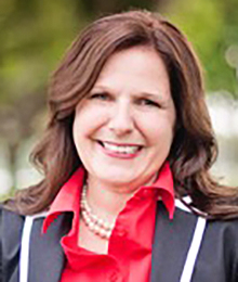 Paige Greenlee headshot, Caucasian female, middle aged with brown hair, wearing a black and white blazer with a red button down shirt and a pearl necklace