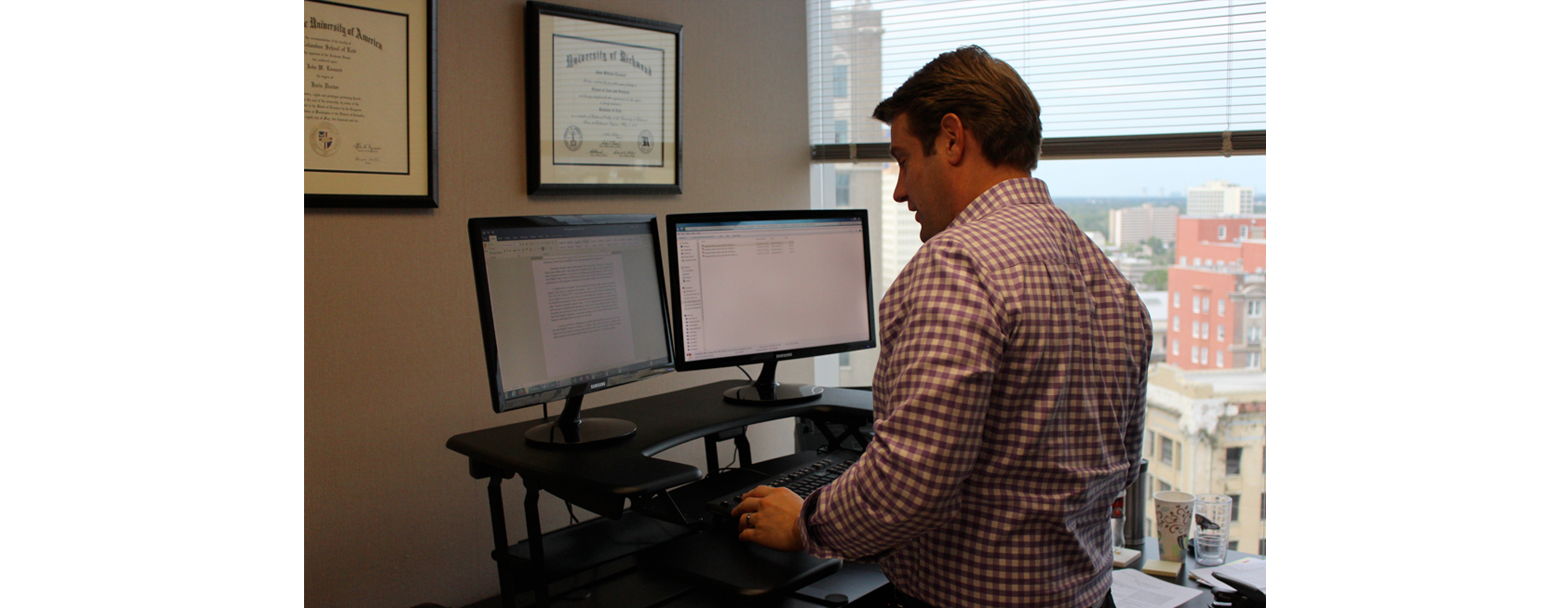 A young businessman is using a stand up desk in an office setting
