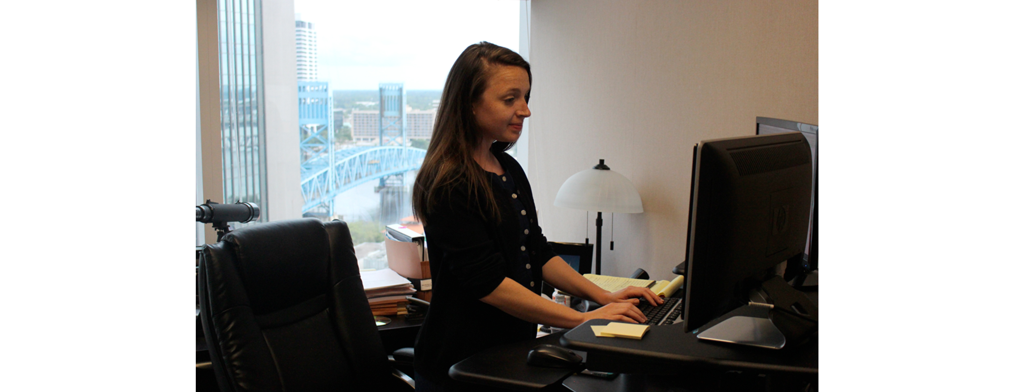A young businesswoman is using a stand up desk in an office setting