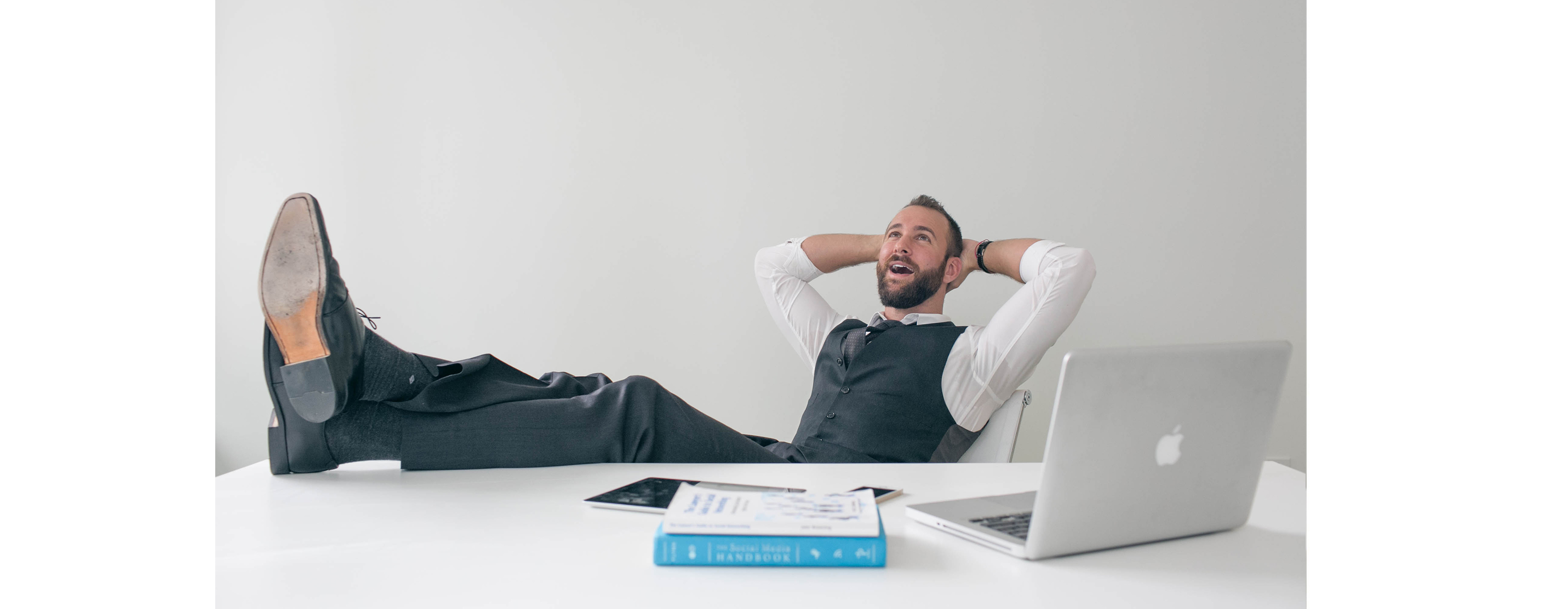 Relaxed businessman sits with his feet up on the desk