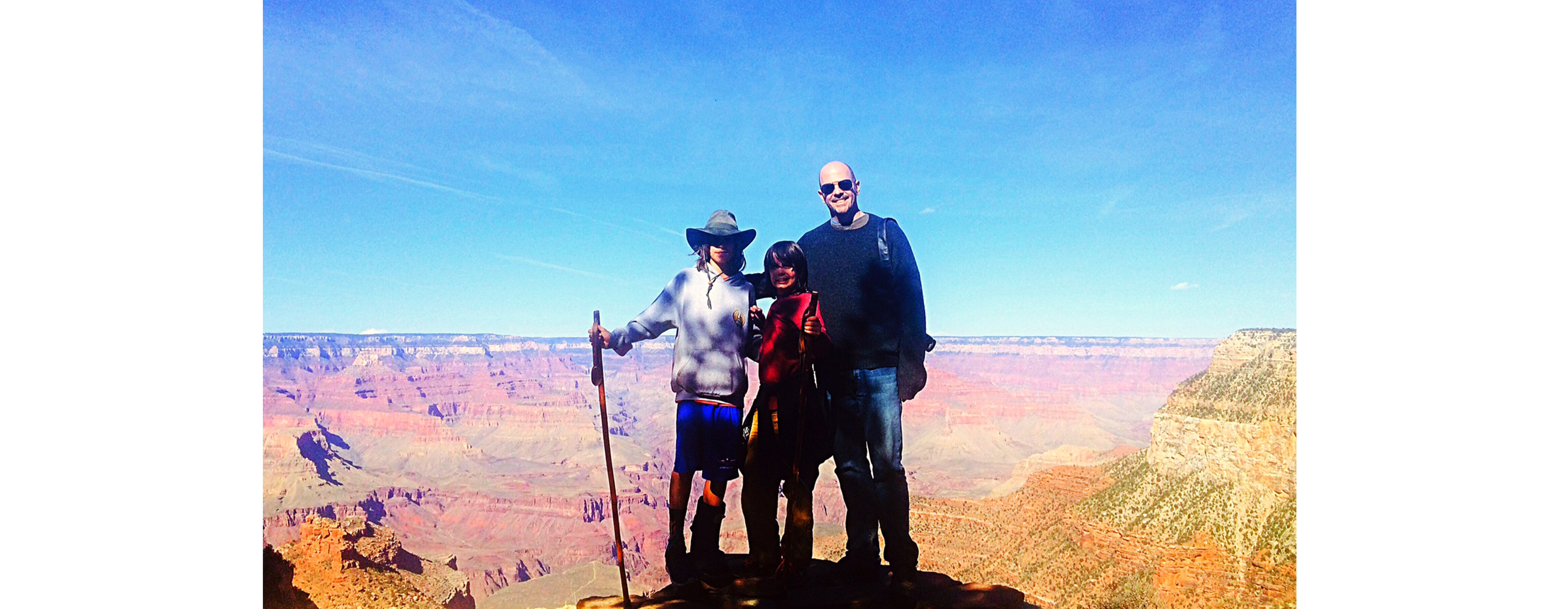 A group of 3 people are standing at the rim of a majestic canyon on a beautiful sunny day