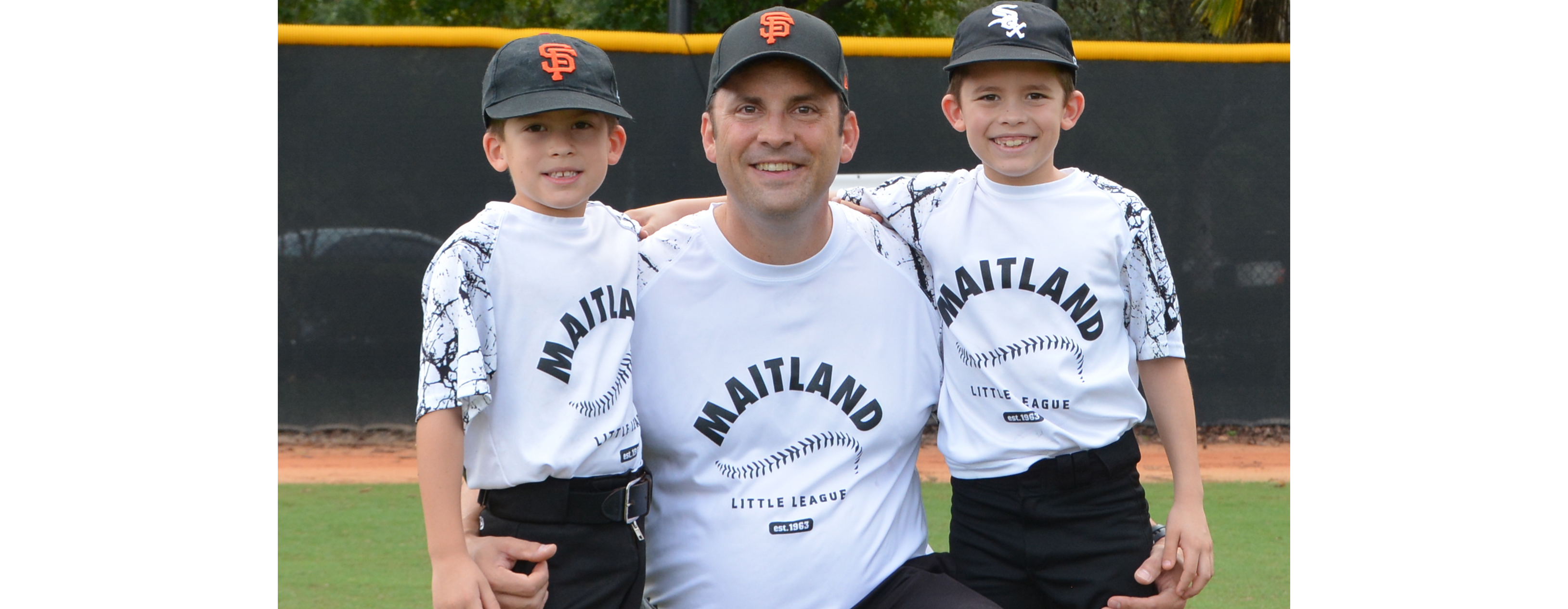 Judge Willis is pictured on the field with two young baseball players