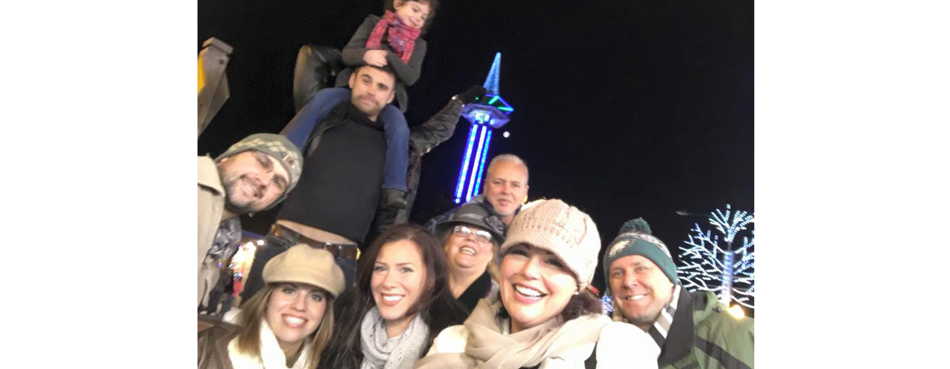 Michelle Suarez is pictured with a group of people outdoors at night in a chilly downtown setting