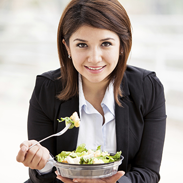 Young businesswoman eats a healthy salad for lunch