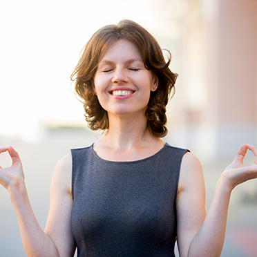 Relaxed woman stands outside, eyes closed, enjoying life