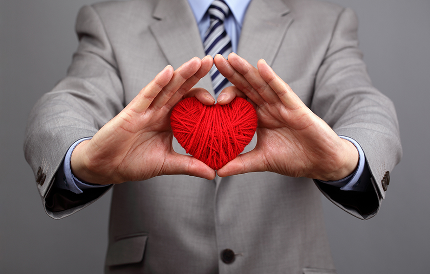 Attorney dressed suit, holding up a yarn heart. Showing heart/love for doing pro bono work.