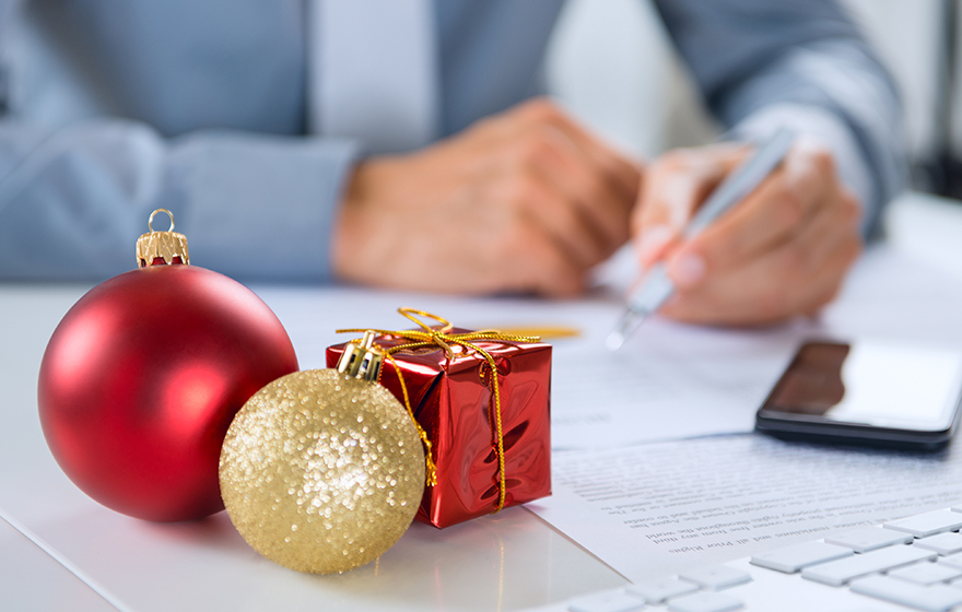 Christmas Ornament In Front Of Businessman Working At Desk