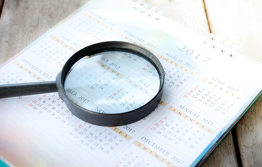 Magnifying glass over a calendar