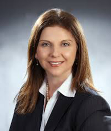 Caucasian female lawyer with light brown hair, wearing a dark black suite and white collared shirt.