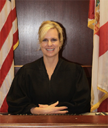 Honorable female judge seated at the bench with a flag on each side of her