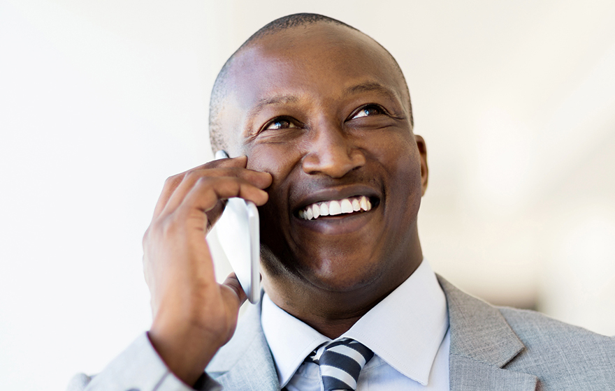 cheerful black businessman talking on smart phone in office