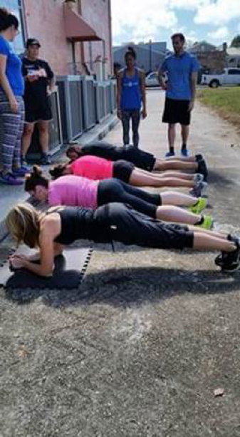 AWKO team exercising and doing planks together outdoors