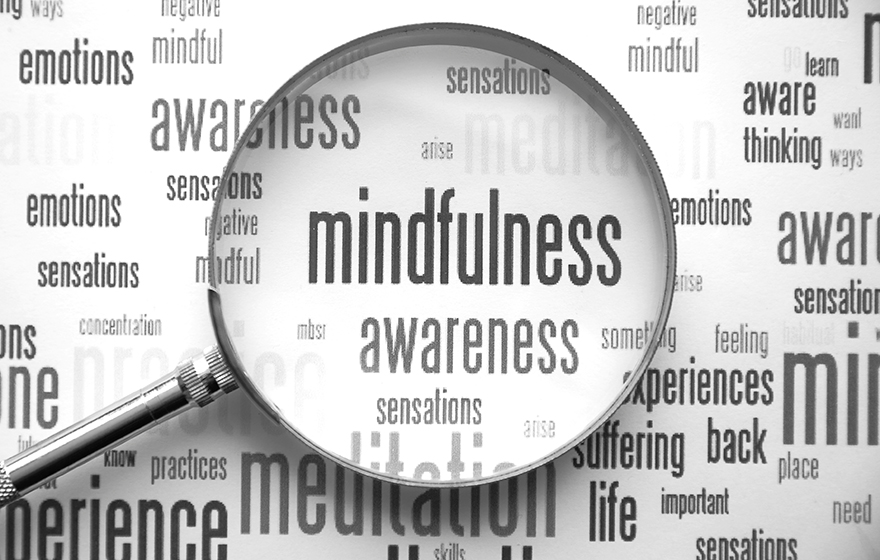 Mindfulness word bubble with magnifying glass laid over top of it