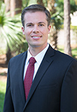 Zack Zuroweste a young Caucasian man in a black suit with a red tie with sunny palm trees in the background