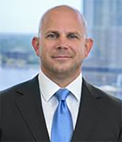 Bill Adams headshot of a bald Caucasian man in a black suit, white shirt and bright blue tie. There is a building and water in the background