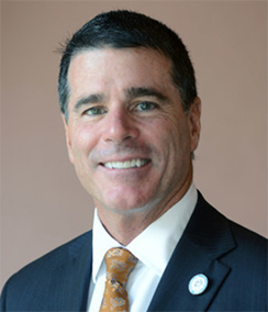 Bill Schifino headshot of a middle aged Caucasian man with dark brown hair wearing a navy blue suit, white shirt, and orange tie