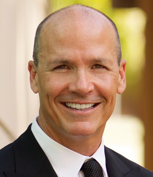 Jason Gunter headshot of a middle aged smiling Caucasian man wearing a black suit and a black dotted tie