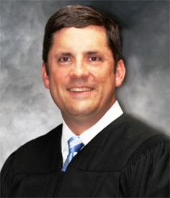 Judge F Rand Wallis headshot of a Caucasian man with brown hair and brown eyes in a black judges' robe with a white shirt and blue striped tie