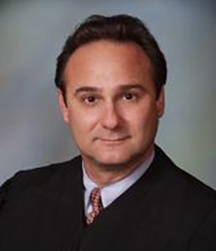 Judge Gary Flower headshot of a middle aged Caucasian man with brown hair and brown eyes in a black judges' robe. He also has a light colored shirt on a maroon tie.