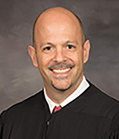 Judge Sam Salario headshot a Caucasian man whom is smiling, he has brown eyes in a black judges' robe with a white shirt and blue striped tie