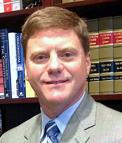 Judge Tim Osterhaus headshot of a middle aged Caucasian man with light brown hair. He is wearing a light grey suit, light colored shirt and blue striped tie. There is a bookshelf with large green books in the background.